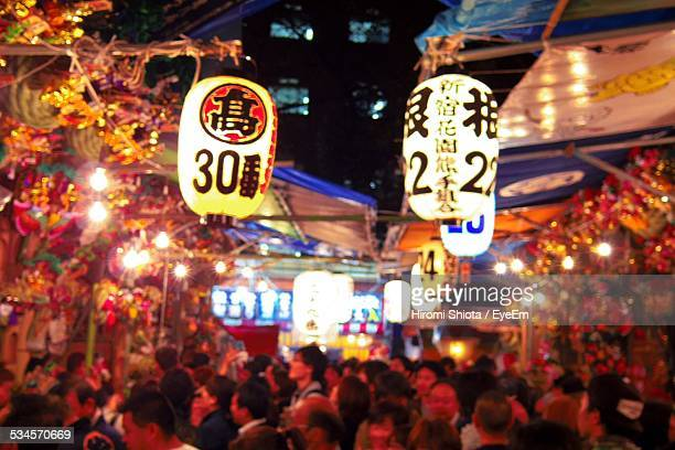 Illuminated Lanterns With Numbers Above Crowd