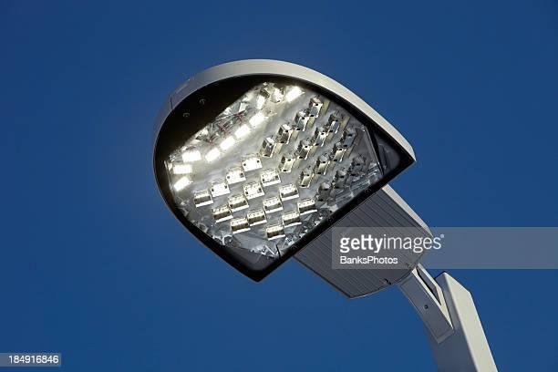 Streetlight LED iluminado contra um céu azul claro