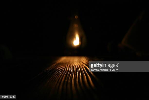 Illuminated Light Bulb Hanging Over Wooden Table In Darkroom