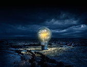 Illuminated light bulb in cracked earth