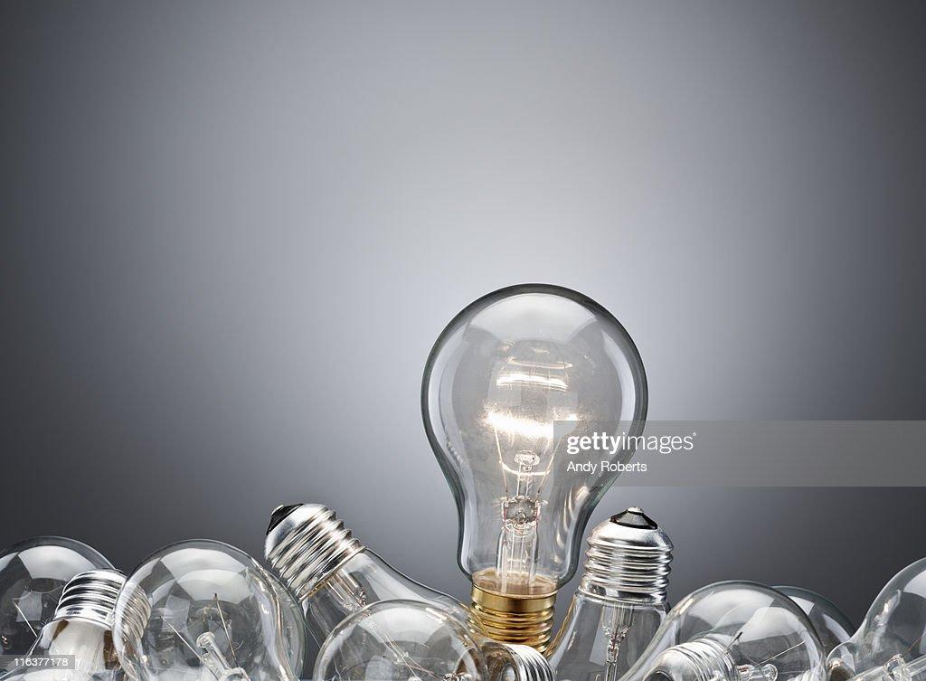 Illuminated light bulb in pile