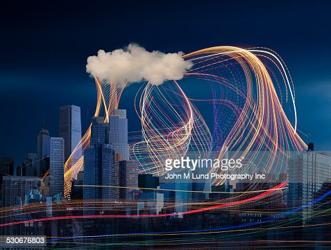 Illuminated light trails and cloud over cityscape