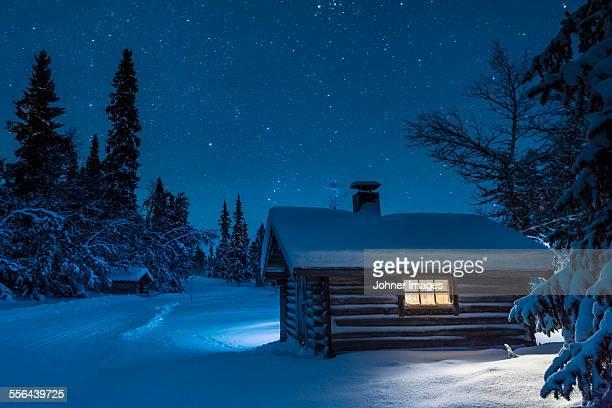 Illuminated log house at night