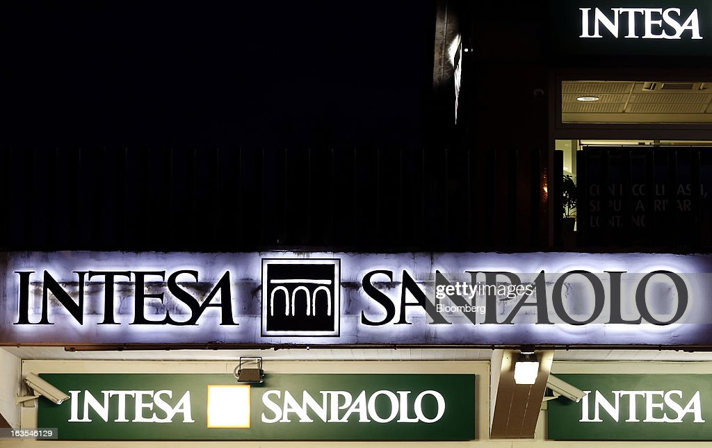Illuminated logos sit above the entrance to an Intesa Sanpaolo SpA bank branch at night in Rome, Italy, on Monday, March 11, 2013. Intesa Sanpaolo SpA and UniCredit SpA are among Italian banks due to report losses for the fourth quarter this week, as the economic contraction meant more clients failed to repay their debts. Photographer: Alessia Pierdomenico/Bloomberg via Getty Images