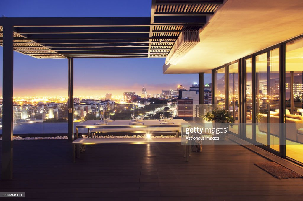 Illuminated luxury house and patio overlooking city