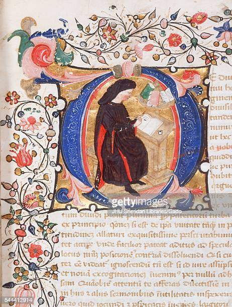 Illuminated manuscript page containing text an ornate border and an illustration of a scribe at work from late 14th century Latin manuscript book...