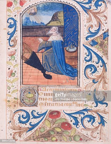 Illuminated manuscript page from 'Tenere et credere me faciat' with illustrations of a man praying with decorative borders book of hours manuscript...
