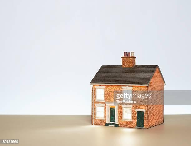 Illuminated model house against blue background