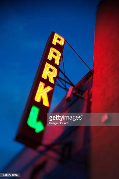 Illuminated neon parking sign on building