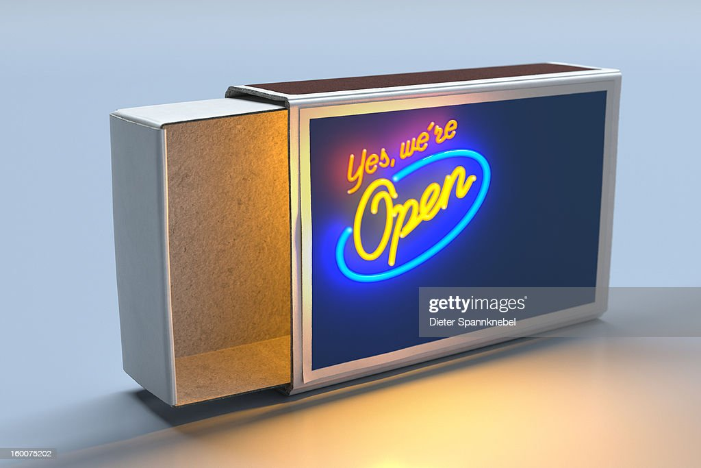 Illuminated neon sign outside of an open matchbox