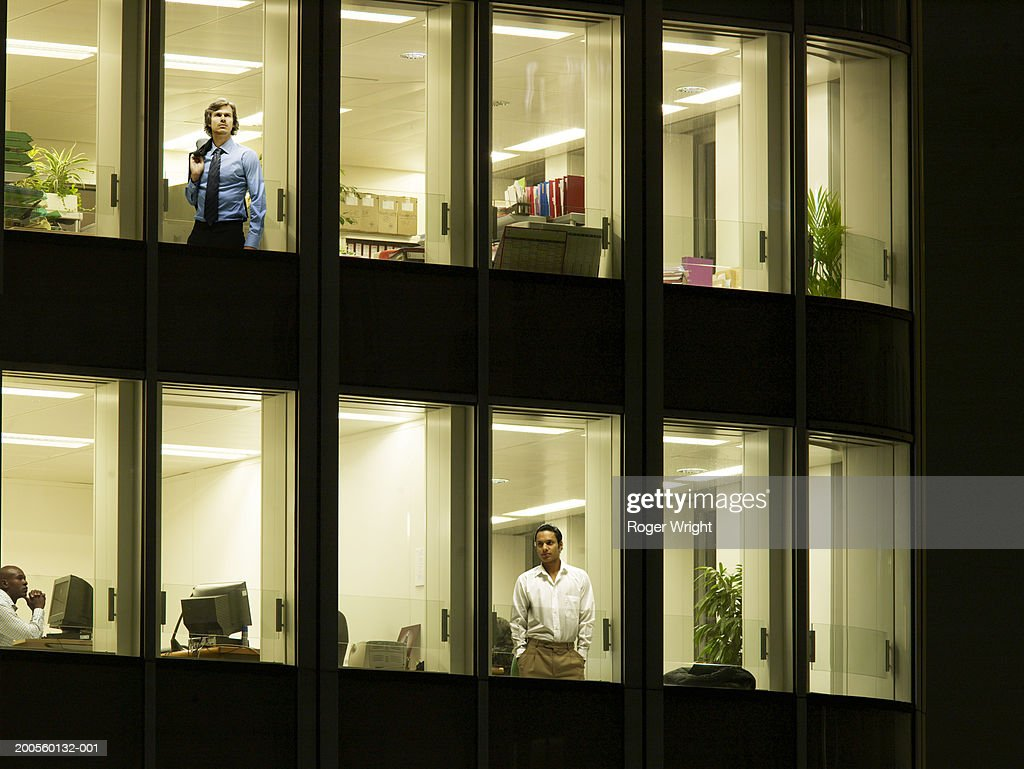 Illuminated office building with workers at window, night : Stock Photo