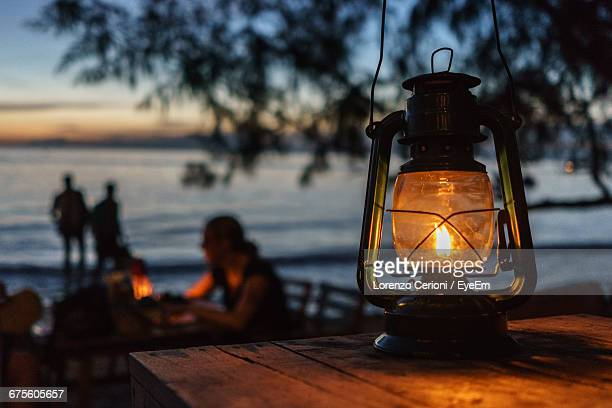Illuminated Old-Fashioned Lantern On Wooden Table At Shore