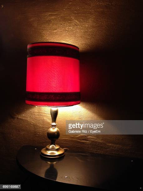 Illuminated Red Lamp On Side Table At Home