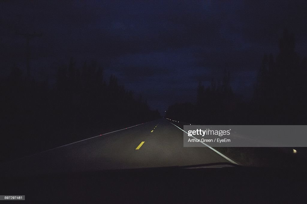Illuminated Road Against Sky Seen From Car Windshield At Night