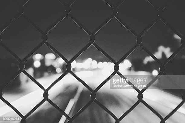 Illuminated Road Seen Through Chainlink Fence At Night