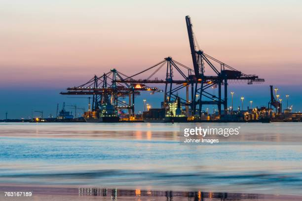 Illuminated shipping cranes at dusk