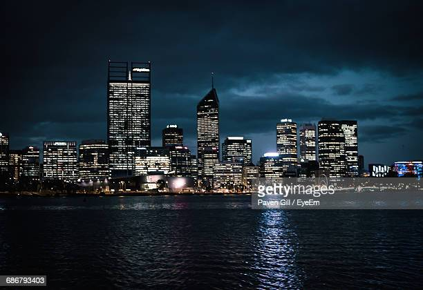 Illuminated Skyscrapers By River Against Cloudy Sky At Night