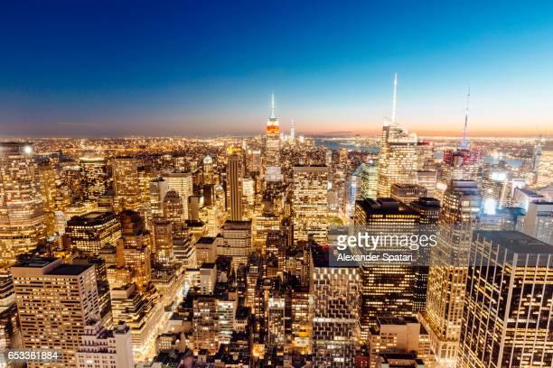 Illuminated skyscrapers of Manhattan at sunset, New York City, USA