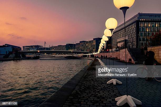 Illuminated Street Light By River At City Against Sky During Sunset