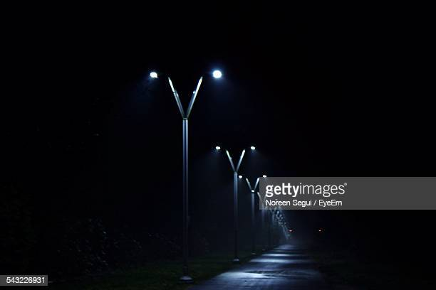Illuminated Street Lights On Road Against Clear Sky At Night