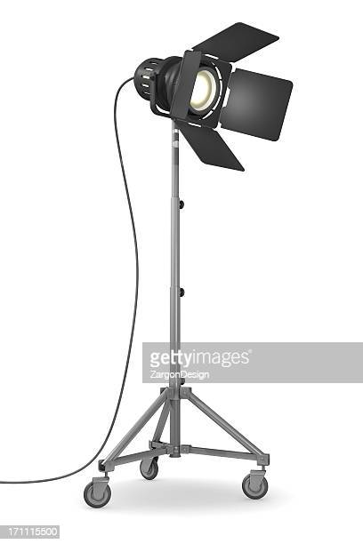 Illuminated studio light on wheels on white background
