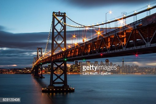 Illuminated Suspension Bridge With Cityscape In Background