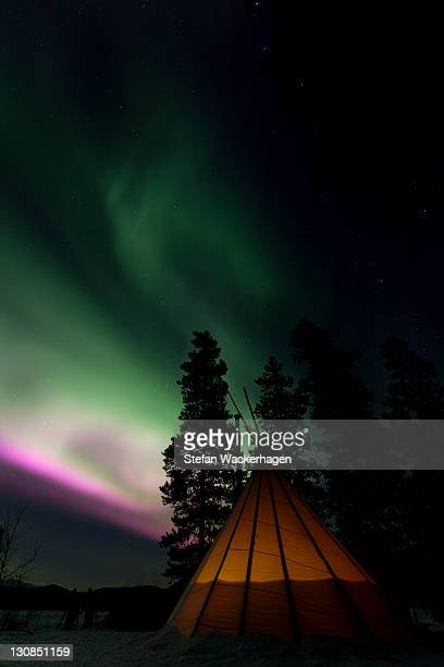 Illuminated teepee, tipi, tepee, northern polar lights (Aurora borealis), green pink purple, near Whitehorse, Yukon Territory, Canada