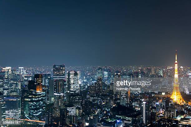 Illuminated Tokyo Tower amidst cityscape against sky at night