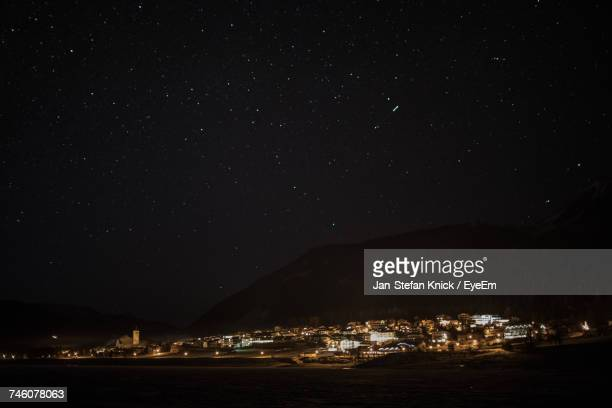 Illuminated Town By Mountain Against Star Field