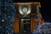 Natural Christmas tree and Triumphal Arch with clock decorated with led lights at night. Winter holidays greeting card. Chisinau, Moldova.