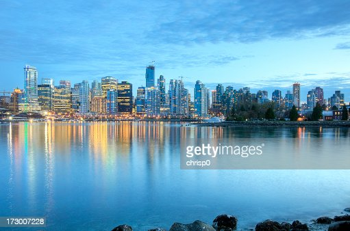 Illuminated Vancouver skyline at dusk as seen from the river