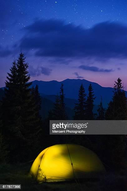 Illuminated yellow camping tent under stars at night Carpathian Landscape