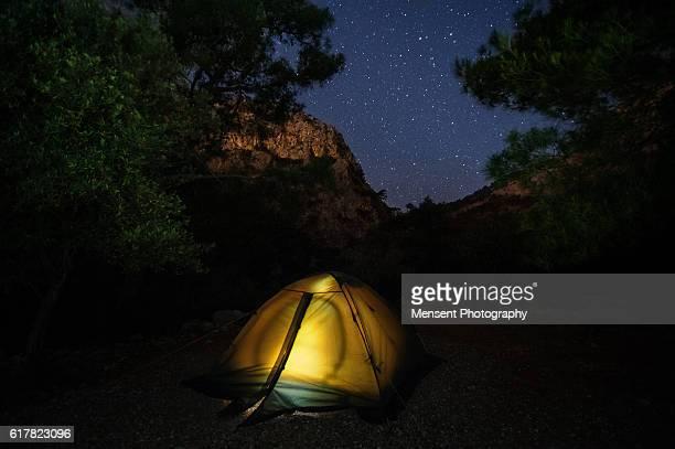Illuminated yellow camping tent under stars at night likya yolu Turkey