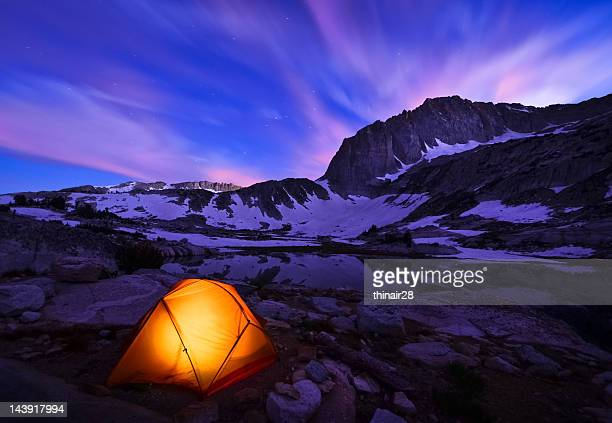 Illuminated yellow tent on snowy mountains range at night