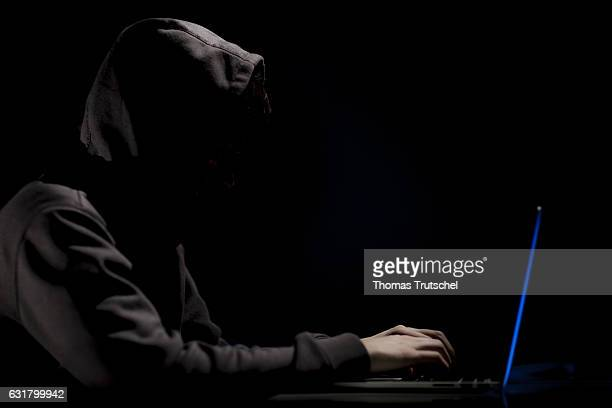 Illustration about 'Darknet' A man with a hood is sitting on a laptop on January 13 2017 in Berlin Germany