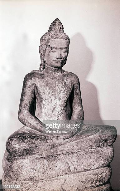 Illustration from the life of the Buddha The seprent Mucilinda makes a seat out of its coils for Buddha to meditate Cambodia Buddhist Bayon style end...