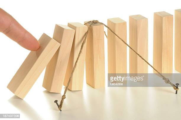 Illustration using tethered wooden dominos for insurance