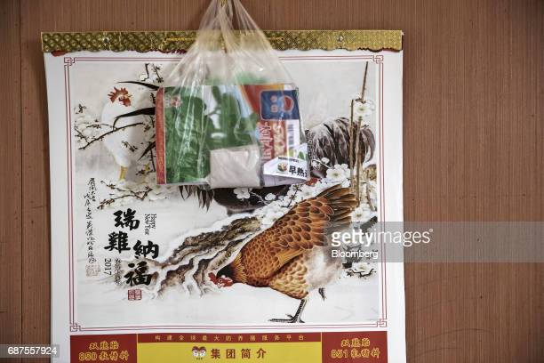 Illustrations of chickens feature on a calendar in the home of a farmer who supplies fresh food to Pifu Ecological Agriculture Ltd near Jiande...