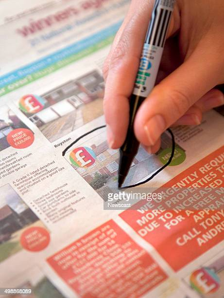 Illustrative image of a person highlighting properties in a newspaper