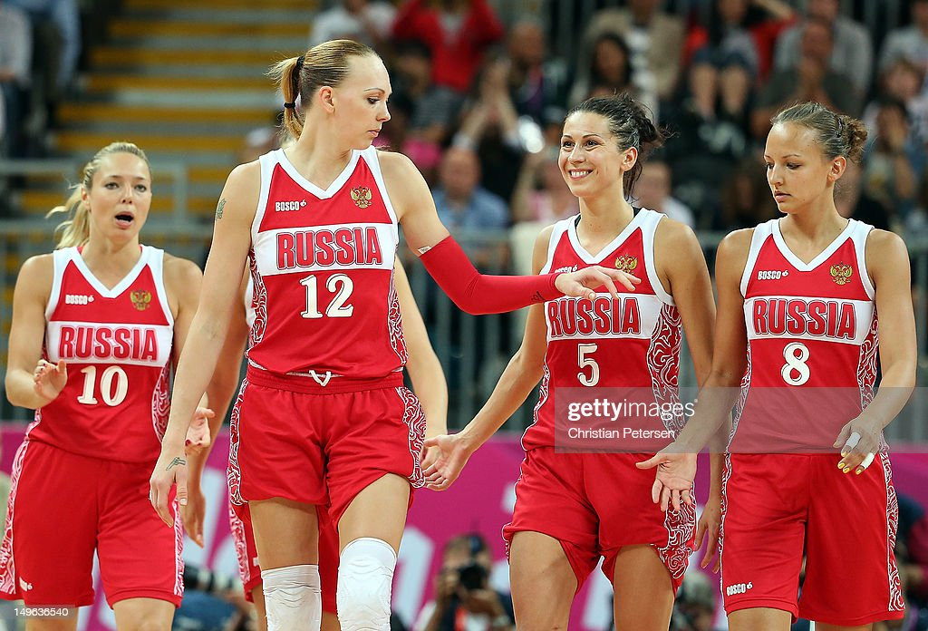 Ilona Korstin #10, Irina Osipova #12, Evgeniya Belyakova #5 and Alena Danilochkina #8 of Russia celebrate after defeating Great Britain in the Women's Basketball Preliminary Round match on Day 5 of the London 2012 Olympic Games at Basketball Arena on August 1, 2012 in London, England.