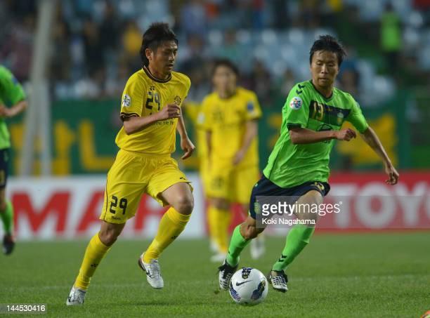 iLRjKoki Mizuno and Hoon Jung of Jeonbuk Hyundai Motors compete for the ball during the AFC Champions League Group H match between Jeonbuk Hyundai...