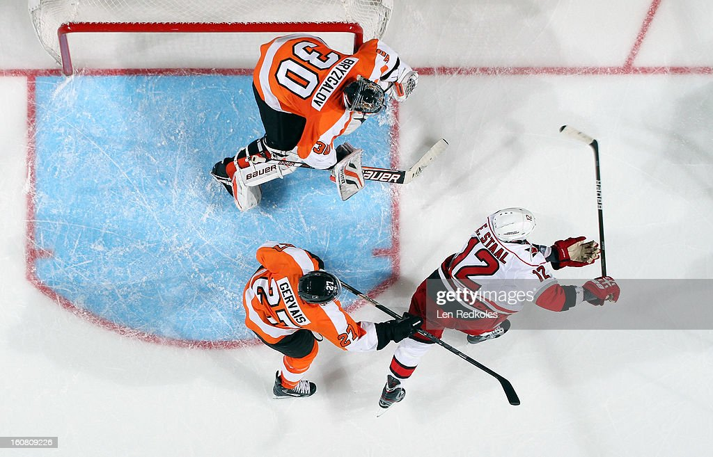 Ilya Bryzgalov #30 and Bruno Gervais #27 of the Philadelphia Flyers prepare to stop a shot on goal by Eric Staal #12 of the Carolina Hurricanes on February 2, 2013 at the Wells Fargo Center in Philadelphia, Pennsylvania.