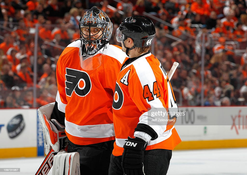 Ilya Bryzgalov confers with Kimmo Timonen #44 of the Philadelphia Flyers during the season opener against the Pittsburgh Penguins at Wells Fargo Center on January 19, 2013 in Philadelphia, Pennsylvania.