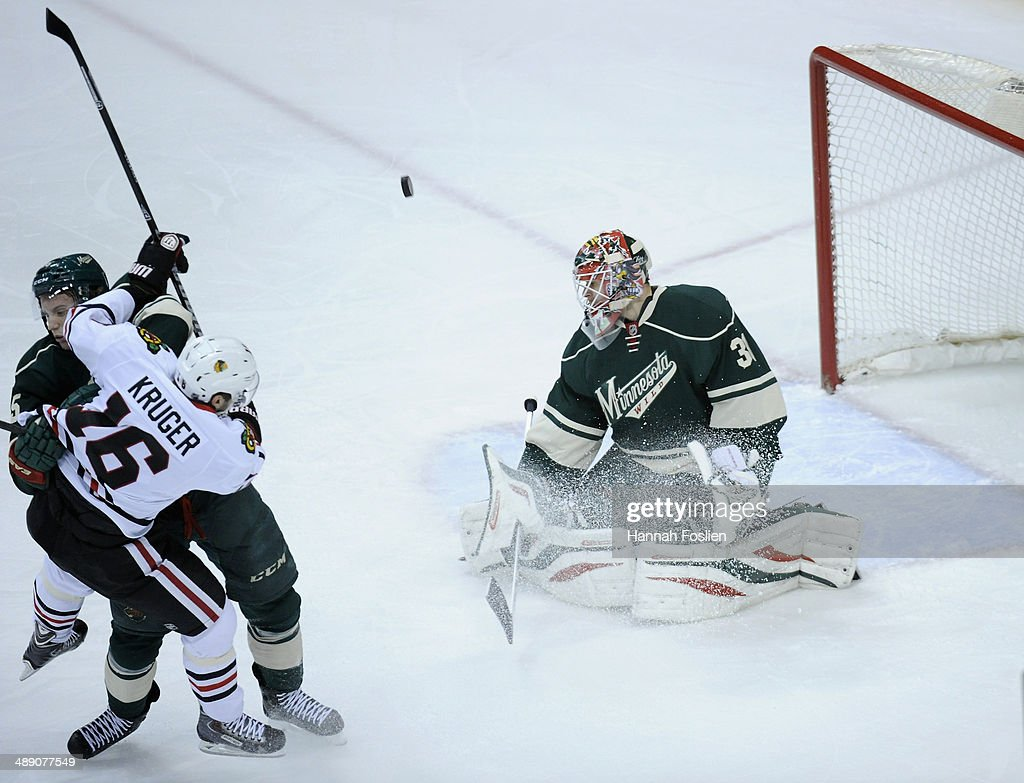 <a gi-track='captionPersonalityLinkClicked' href=/galleries/search?phrase=Ilya+Bryzgalov&family=editorial&specificpeople=2285430 ng-click='$event.stopPropagation()'>Ilya Bryzgalov</a> #30 of the Minnesota Wild deflects the puck as teammate <a gi-track='captionPersonalityLinkClicked' href=/galleries/search?phrase=Jonas+Brodin&family=editorial&specificpeople=7832272 ng-click='$event.stopPropagation()'>Jonas Brodin</a> #25 of the Minnesota Wild stops the progress of Marcus Kruger #16 of the Chicago Blackhawks during the first period in Game Four of the Second Round of the 2014 NHL Stanley Cup Playoffs on May 9, 2014 at Xcel Energy Center in St Paul, Minnesota. The Wild defeated the Blackhawks 4-2.