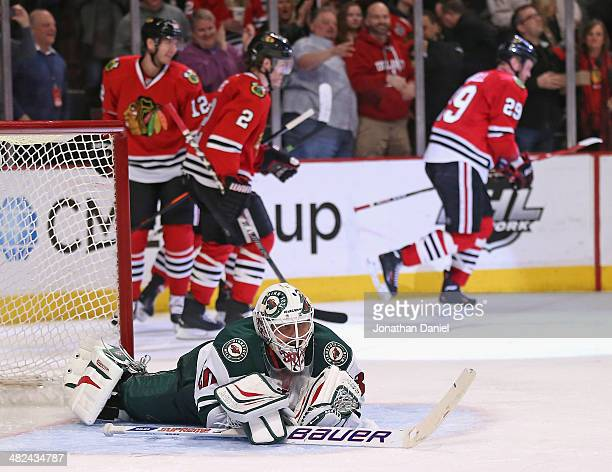 Ilya Bryzgalov of the Minnesota Wild lays on the ice after Bryan Bickell of the Chicago Blackhawks scored a goal in the third period at the United...