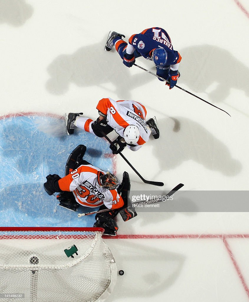 <a gi-track='captionPersonalityLinkClicked' href=/galleries/search?phrase=Ilya+Bryzgalov&family=editorial&specificpeople=2285430 ng-click='$event.stopPropagation()'>Ilya Bryzgalov</a> #30 of the Philadelphia Flyers handles the puck as <a gi-track='captionPersonalityLinkClicked' href=/galleries/search?phrase=John+Tavares&family=editorial&specificpeople=601791 ng-click='$event.stopPropagation()'>John Tavares</a> #91 of the New York Islanders looks for a rebound at the Nassau Veterans Memorial Coliseum on March 15, 2012 in Uniondale, New York. The Flyers defeated the Islanders 3-2.