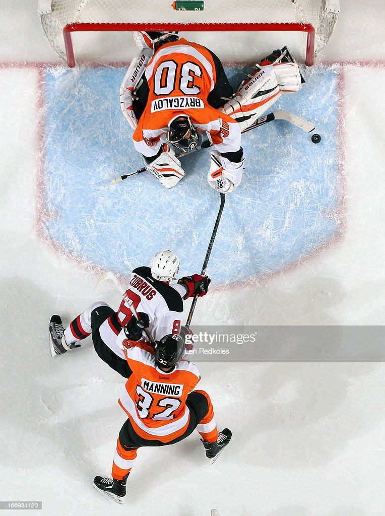 <a gi-track='captionPersonalityLinkClicked' href=/galleries/search?phrase=Ilya+Bryzgalov&family=editorial&specificpeople=2285430 ng-click='$event.stopPropagation()'>Ilya Bryzgalov</a> #30 of the Philadelphia Flyers makes a stick save as teammate Brandon Manning #32 battles with <a gi-track='captionPersonalityLinkClicked' href=/galleries/search?phrase=Dainius+Zubrus&family=editorial&specificpeople=204779 ng-click='$event.stopPropagation()'>Dainius Zubrus</a> #8 of the New Jersey Devils in the crease on April 18, 2013 at the Wells Fargo Center in Philadelphia, Pennsylvania. The Devils went on to defeat the Flyers 3-0.