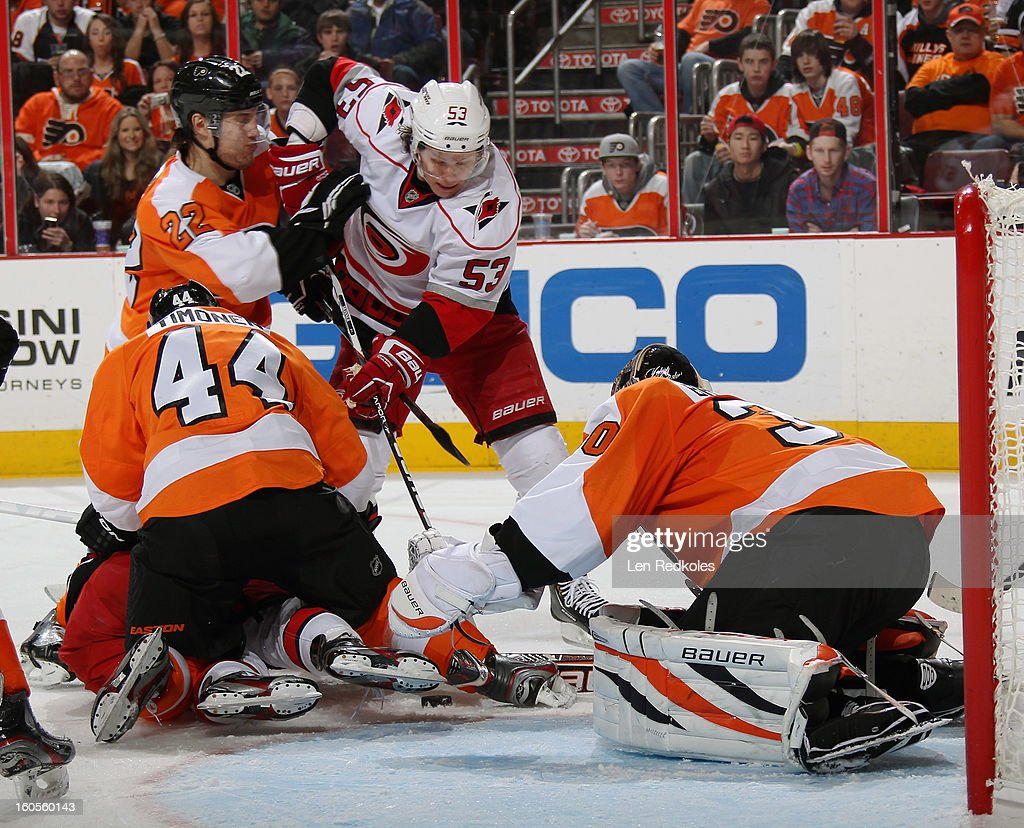 Ilya Bryzgalov #30 of the Philadelphia Flyers reaches for the loose puck while Kimmo Timonen #44 and Luke Schenn #22 defend against Jeff Skinner #53 of the Carolina Hurricanes on February 2, 2013 at the Wells Fargo Center in Philadelphia, Pennsylvania.