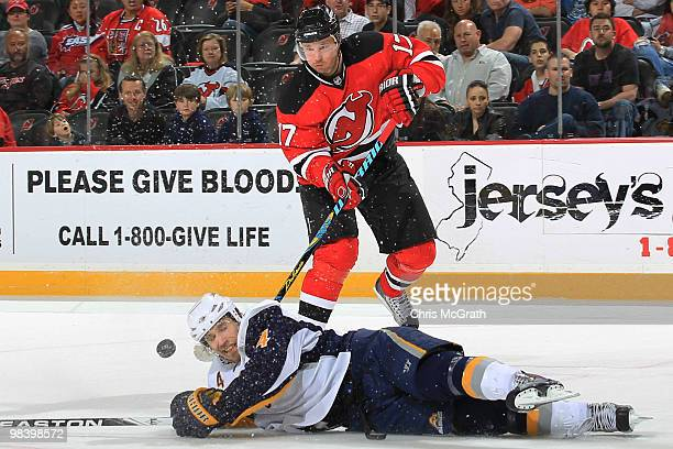 Ilya Kovalchuk of the New Jersey Devils gets a pass away under pressure from Steve Montador of the Buffalo Sabres at the Prudential Center on April...