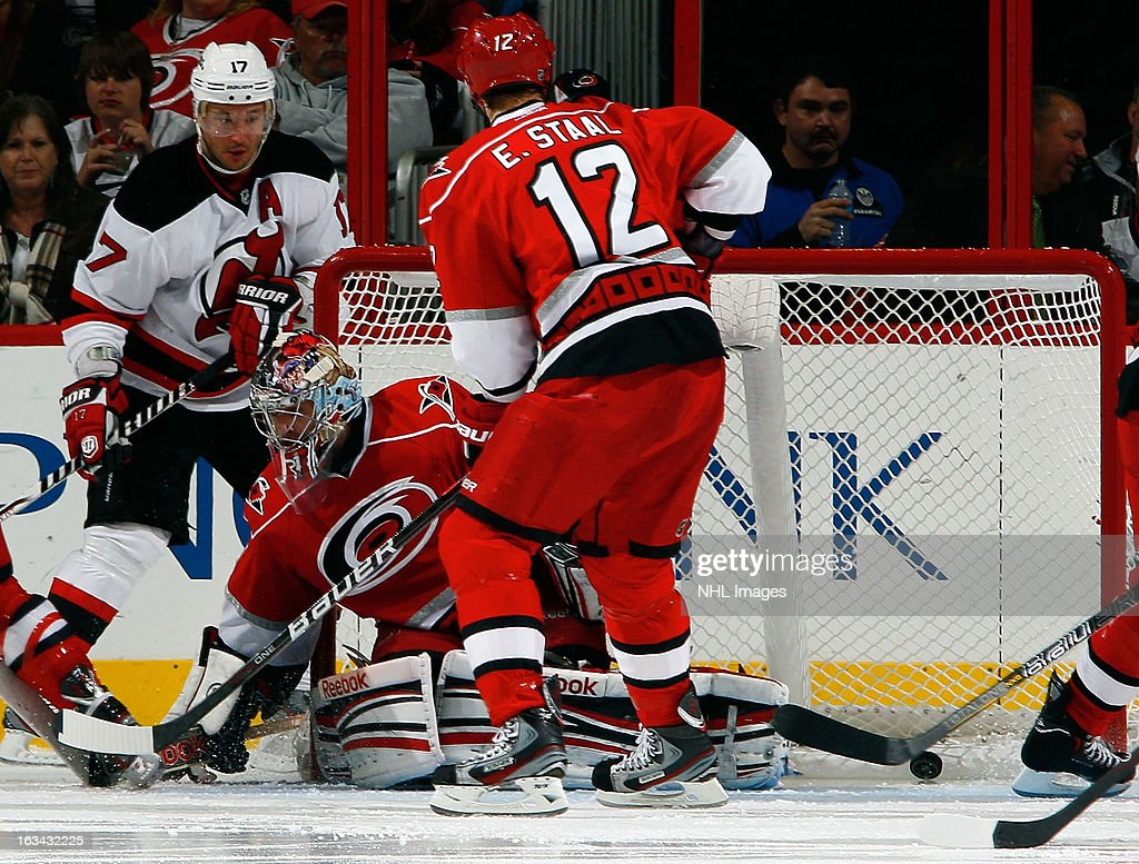 <a gi-track='captionPersonalityLinkClicked' href=/galleries/search?phrase=Ilya+Kovalchuk&family=editorial&specificpeople=201796 ng-click='$event.stopPropagation()'>Ilya Kovalchuk</a> #17 of the New Jersey Devils manages to score a goal on <a gi-track='captionPersonalityLinkClicked' href=/galleries/search?phrase=Dan+Ellis&family=editorial&specificpeople=2235265 ng-click='$event.stopPropagation()'>Dan Ellis</a> #31 of the Carolina Hurricanes from behind the goal line as Eric Staal #12 looks on early in the third period of an NHL game on March 9, 2013 at PNC Arena in Raleigh, North Carolina.
